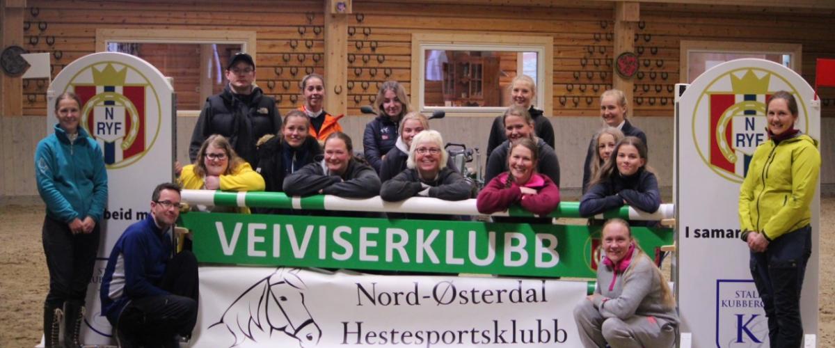 Hestesportsklubben i ridehus foran plakat som det står veiviserklubb på